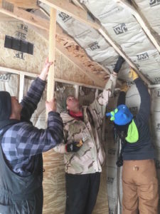 Mekasi, Matthew and Lyssa insulate a solar barn.