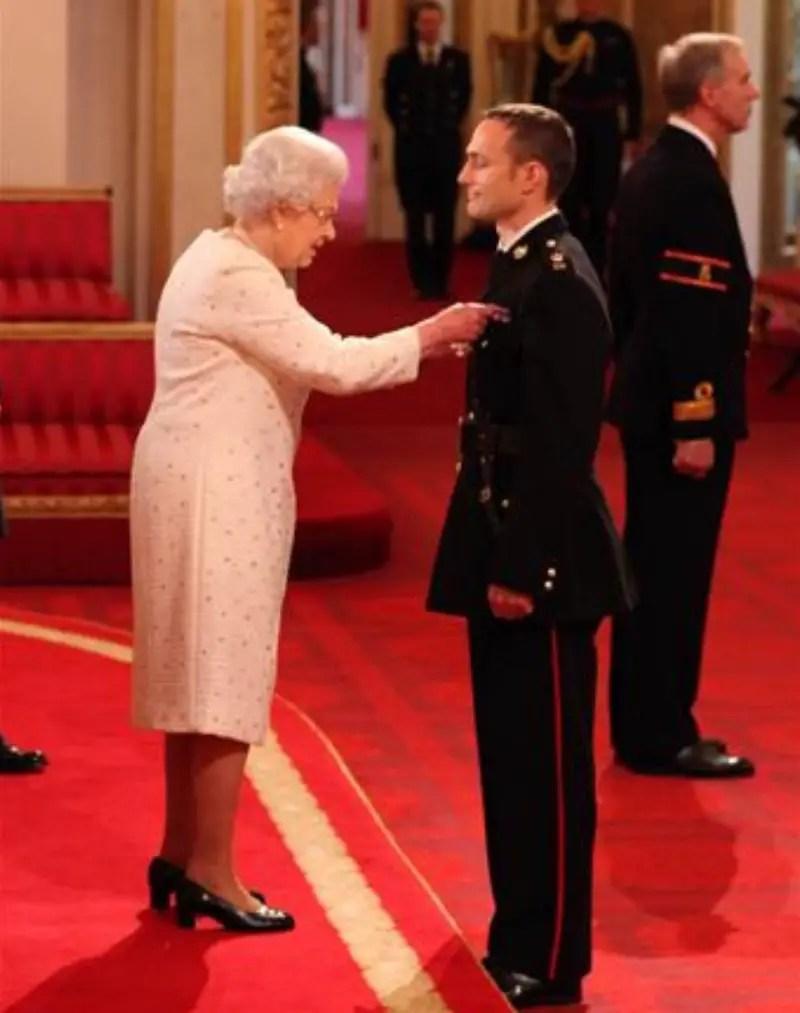 Niki Richard Dalgliesh Cavill in front of Queen Elizabeth II