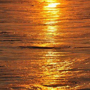 (C) Jule Reiselust: Die untergehende Sonne spiegelt sich im Watt.