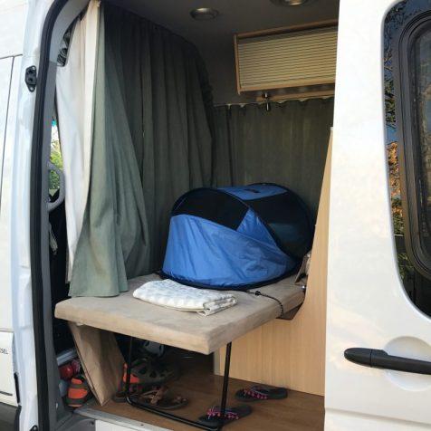 (C) Jule Reiselust: Reisebett im Camper auf dem dritteän Bett mit Spanngurten befestigt.