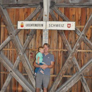 (C) Jule Reiselust: Ulli und Noah auf der Rheinbrücke bei der Flussmitte. Hier verläuft die Grenze von Lichtenstein zur Schweiz.