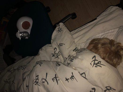 Billede af et barn der ligger i sin seng. Ved siden af står der et ud, udformet som et får der ligger ned. Fåret har lukkede øjne og urskiven er mørk.