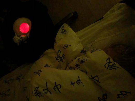Billede af et barn der ligger i en seng. Ved siden af står et ur, udformet som et får der ligger ned. Urskiven er oplyst med rød farve og fårets øjne er lukkede, for at signalere at det er nat.