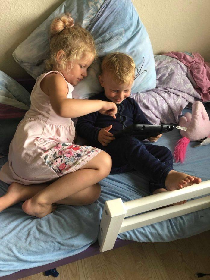 To børn spiller ipad. Den store hjælper den lille. De sidder i en seng.