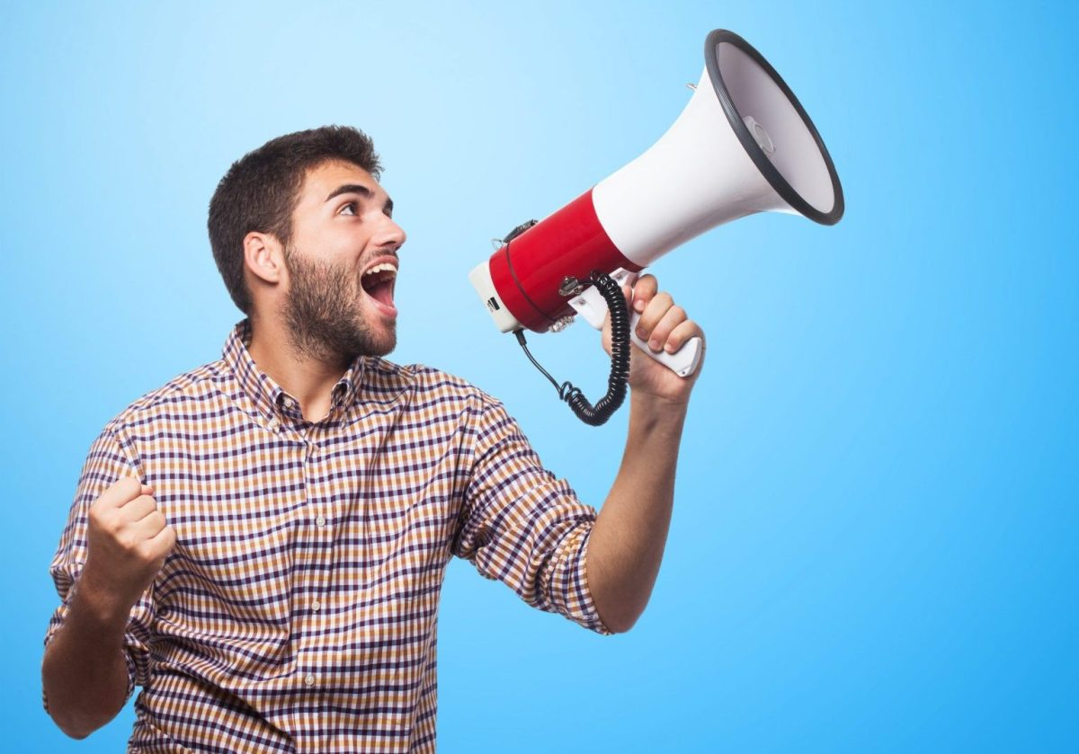 portrait of a handsome man shouting with a megaphone