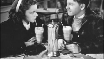 Young Judy Garland has a soda with young Mickey Rooney at the soda shop