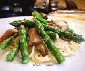 Asparagus and oyster mushrooms on top of spaghetti.