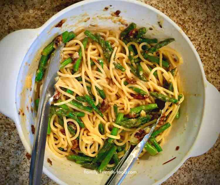 Asparagus carbonara in a dish with tongs.