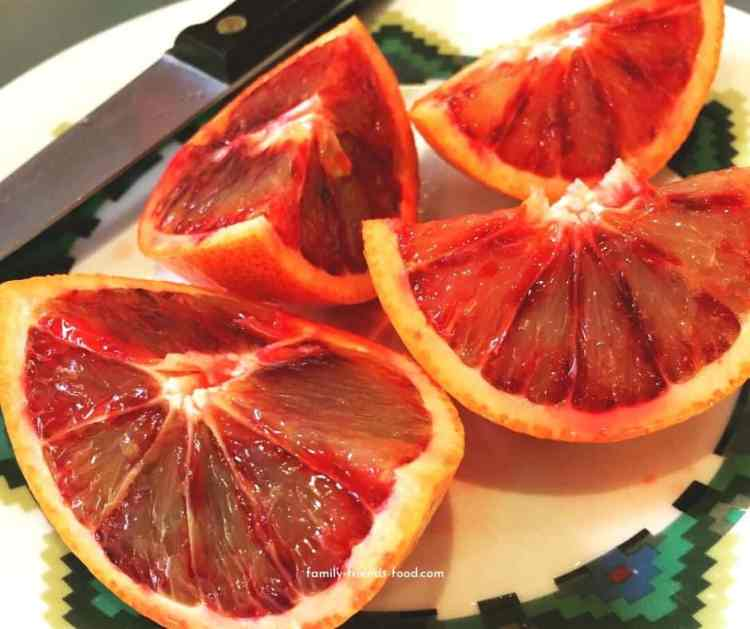 Cut up blood orange on a plate.