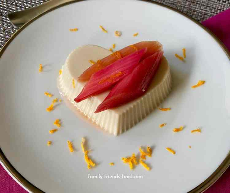 Vegan panna cotta with roasted rhubarb on white plate.