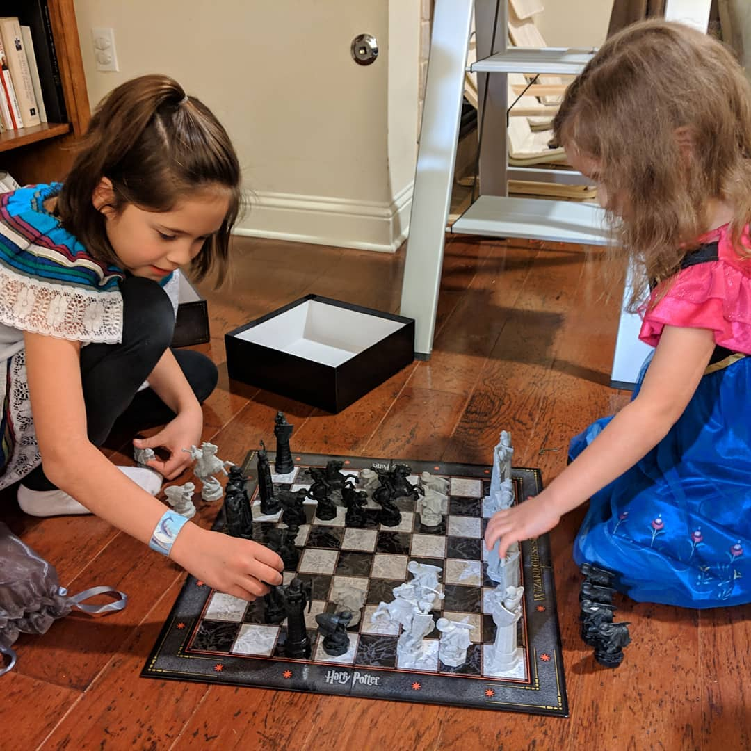 Catalina teaching Ana (while she's wearing her Frozen Princess Anna's pajamas) how to play chess on a Harry Potter board