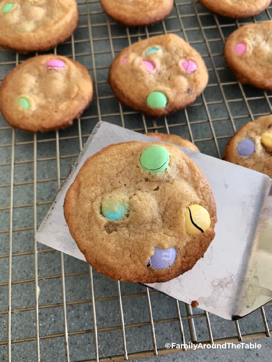 M & M cookie on a spatula with more on a cooling rack.