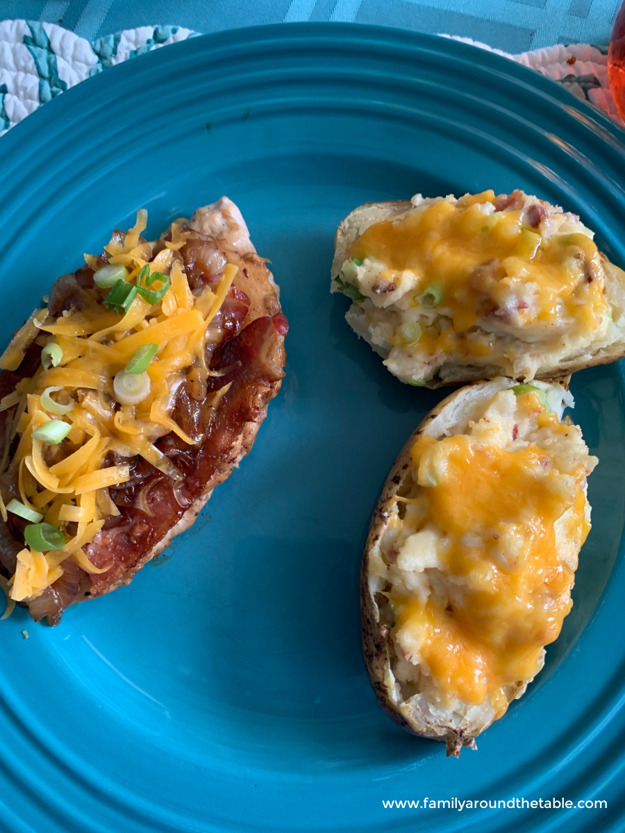 2 twice baked potatoes on a plate with main dish.