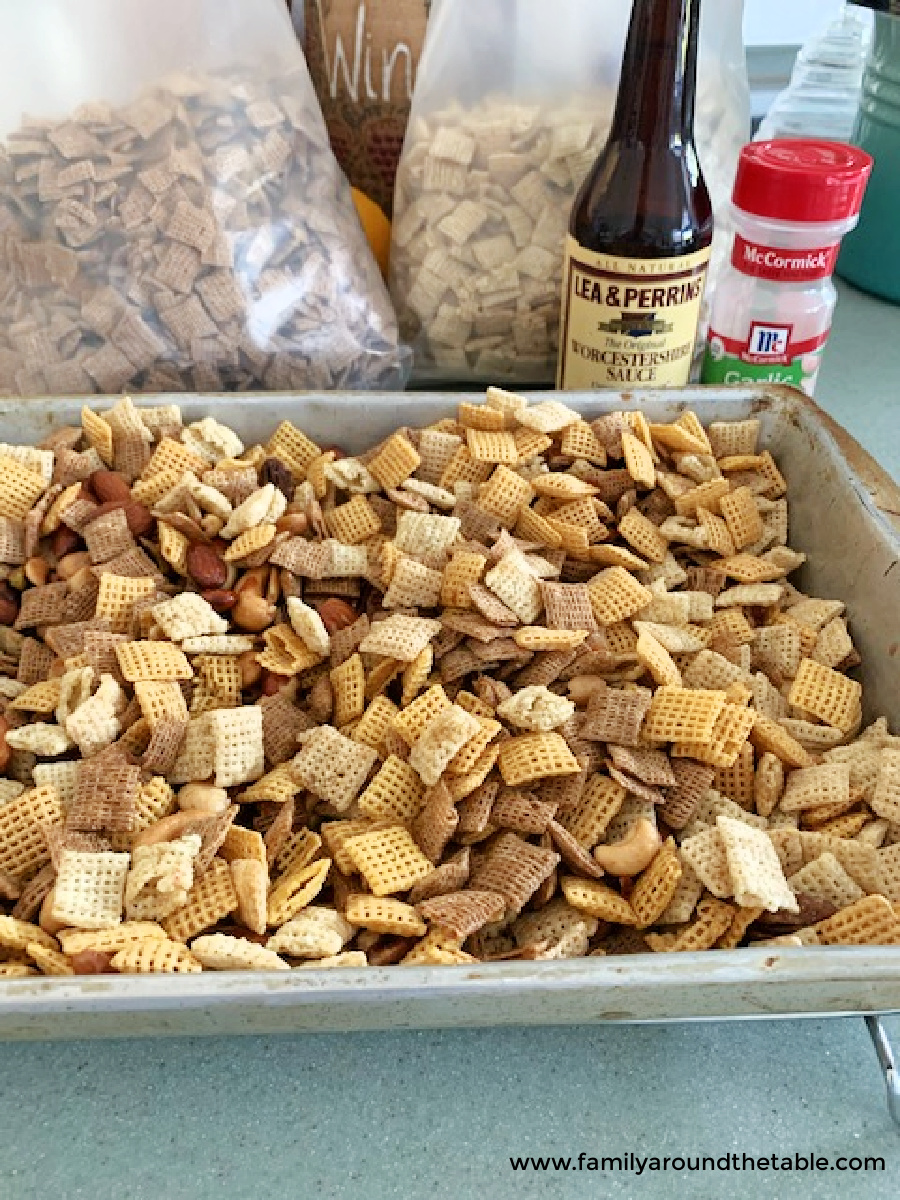 The ingredients for Chex mix in a silver pan.