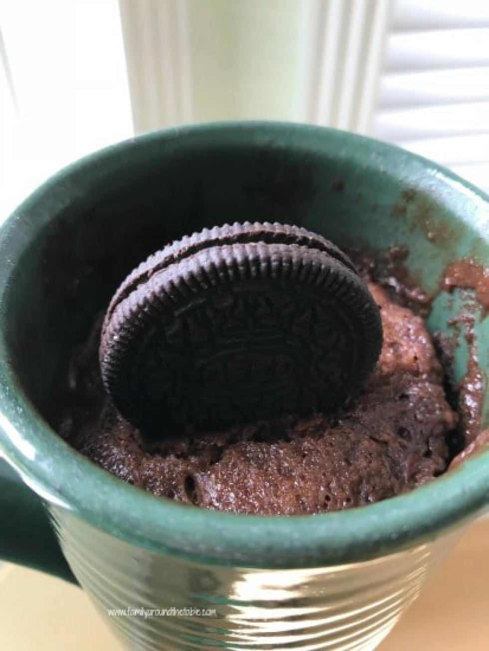 Chocolate mug cake in a green mug with Oreo on top.