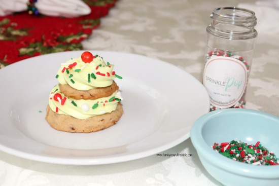 One brown sugar pecan Christmas tree cookie on a white plate with sprinkles in a bowl.