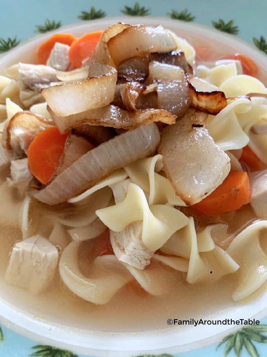 A bowl of chicken noodle soup garnished with caramelized onions.