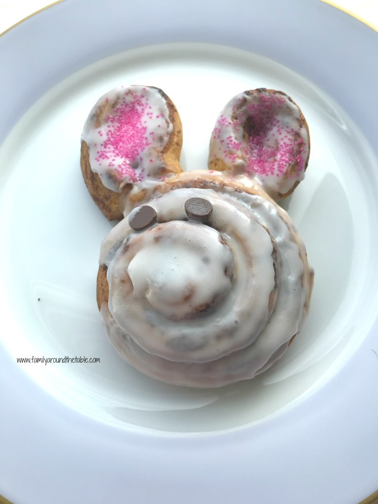 A cinnamon roll shaped like a bunny on a white plate.