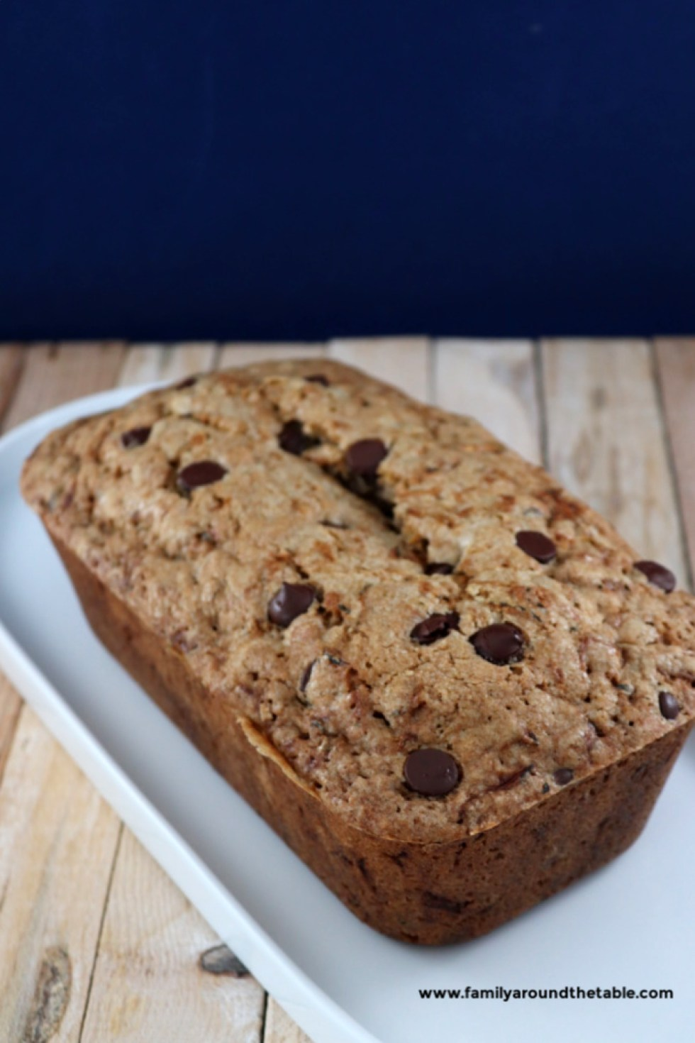 Chocolate chip zucchini bread on a white platter.