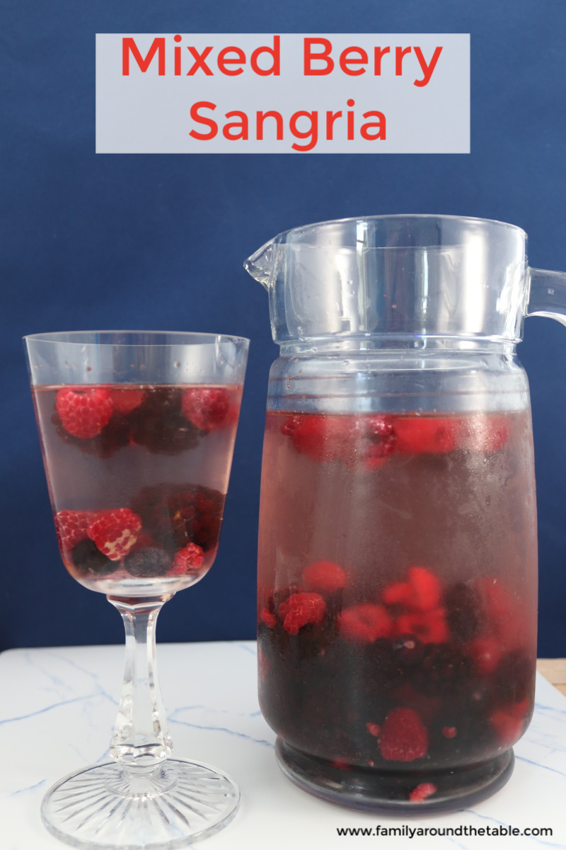 Mixed berry sangria is in a glass and pitcher.