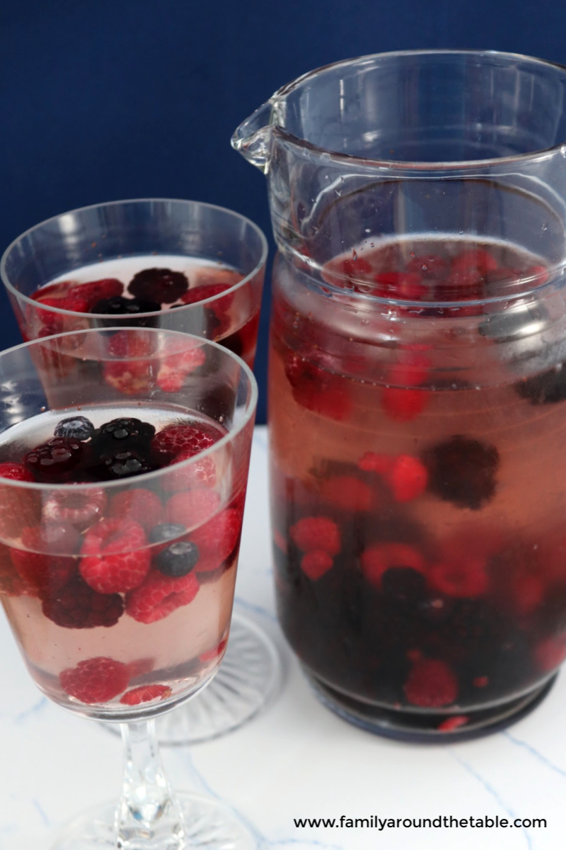 Refreshing mixed berry sangria in glasses and a pitcher.