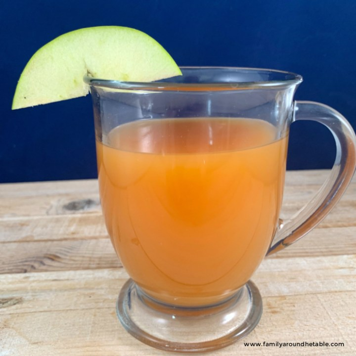 Caramel apple bourbon hot toddy in a clear mug.