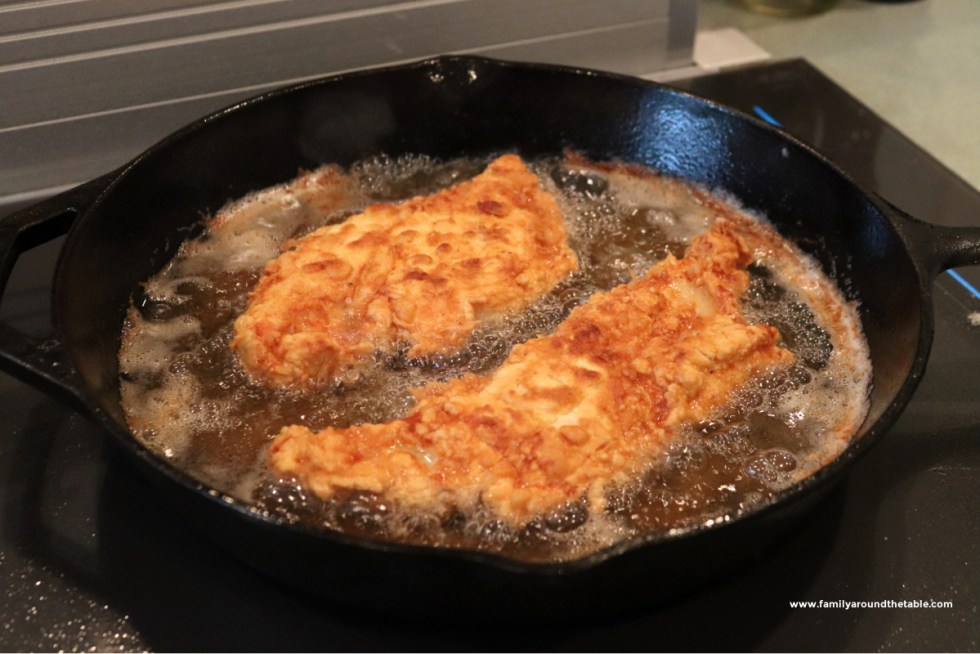 Chicken breast in oil in a cast iron pan.