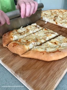 Roasted garlic and chicken white pizza slices on a cutting board.