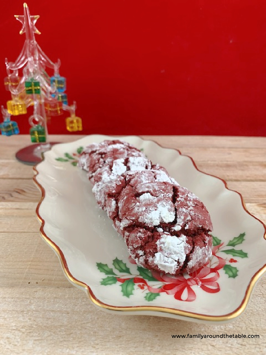 Red velvet crinkle cookies on a holiday plate with a glass Christmas tree in the background.