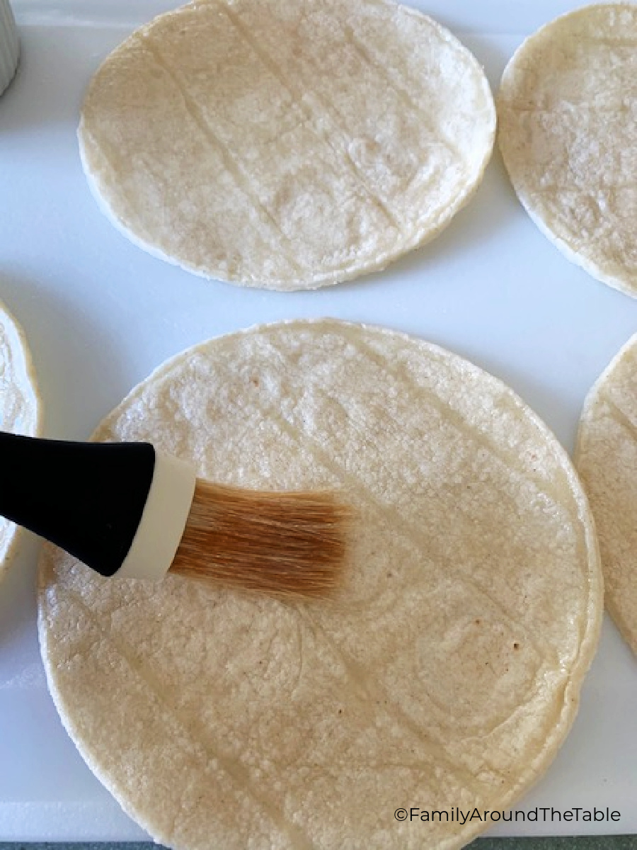 A corn tortilla on a white surface being brushed with oil.