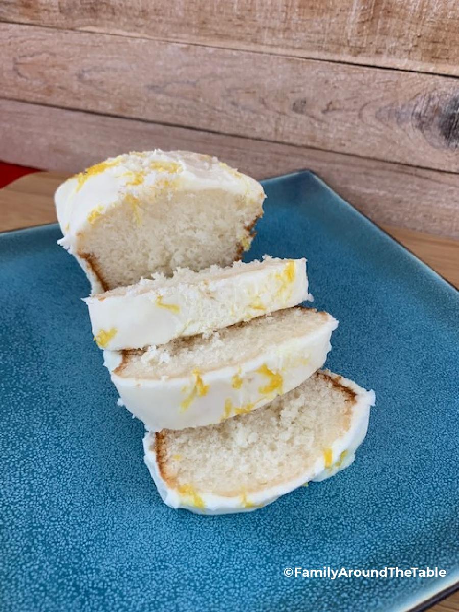 A glazed lemon cake sliced on a blue plate.