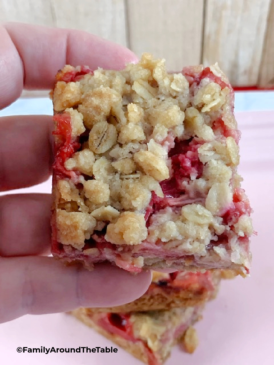 A square strawberry rhubarb oat bar being held.