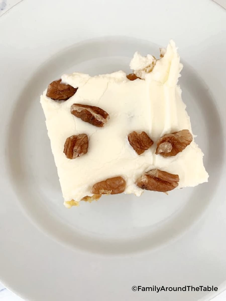 Overhead photo of a piece of cake with pecans on the frosting on a white plate.