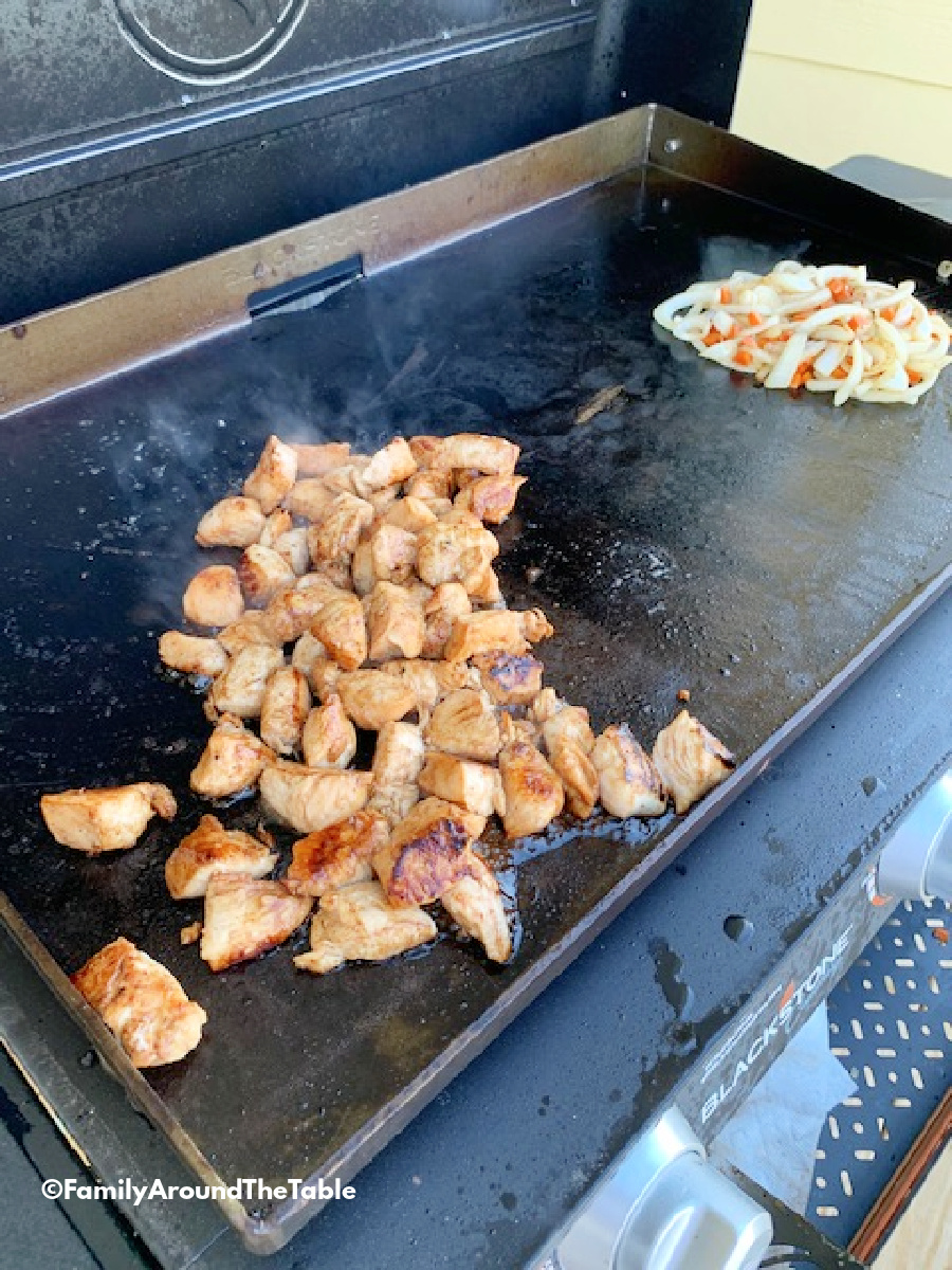 Chicken, onions and carrots cooking on a flat top grill.