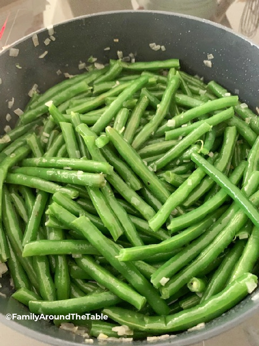 Overhead photo of string beans with shallots in a pan.