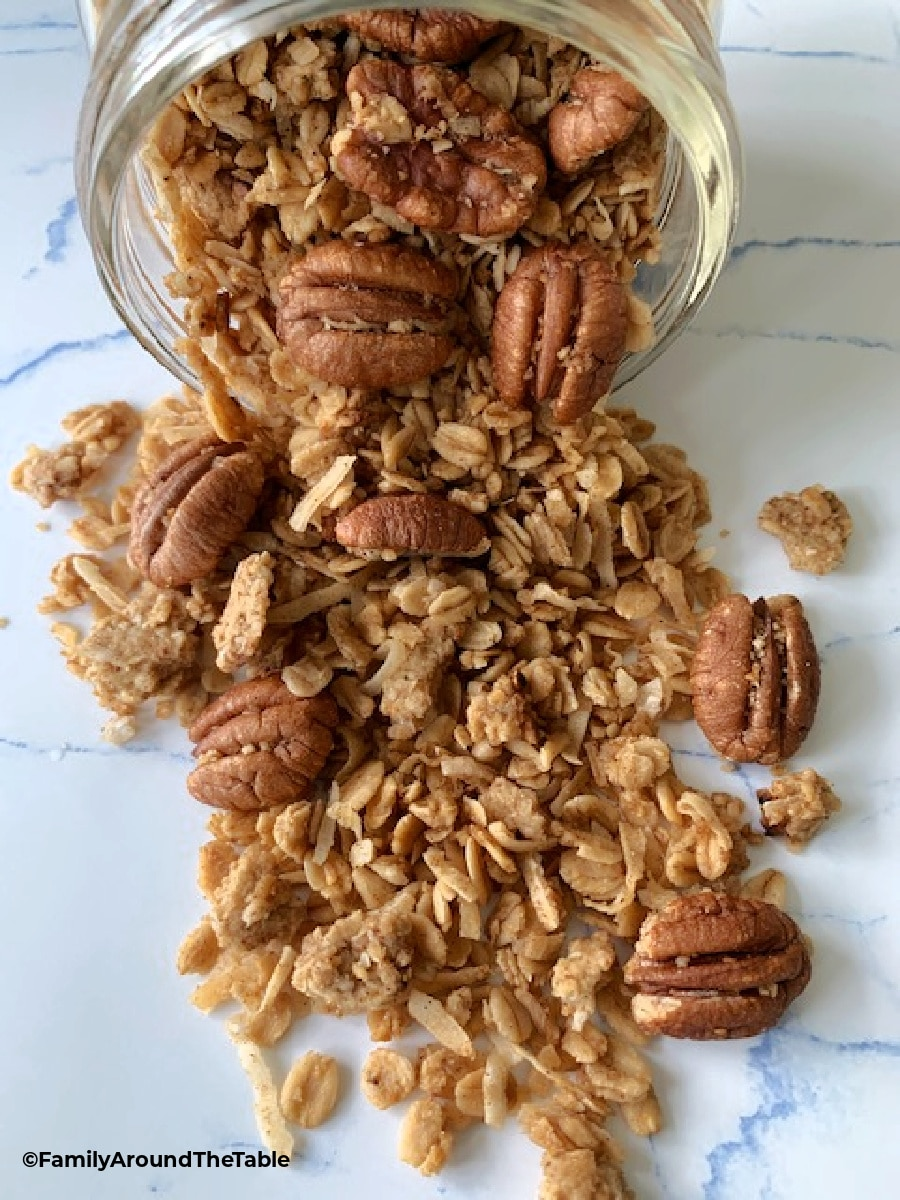 Granola spilling out of a glass jar.