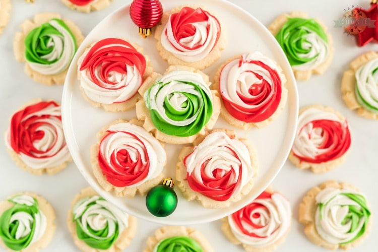 Frosted Rose Sugar Cookies are buttery, soft sugar cookies with a delicious swirled rosette on top! This sugar cookie recipe doesn't require any chilling and you don't have to roll them out either! Elegant Sugar Cookies that look like roses that are perfect as gifts!