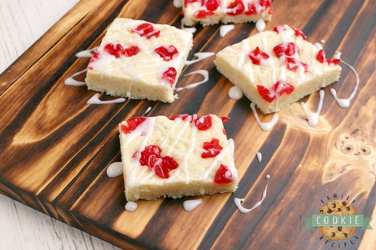 Sugar cookie bar topped with maraschino cherries and glaze