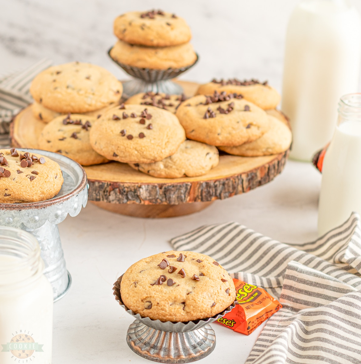 chocolate chip cookies on display trays with a glass of milk and reese's cups