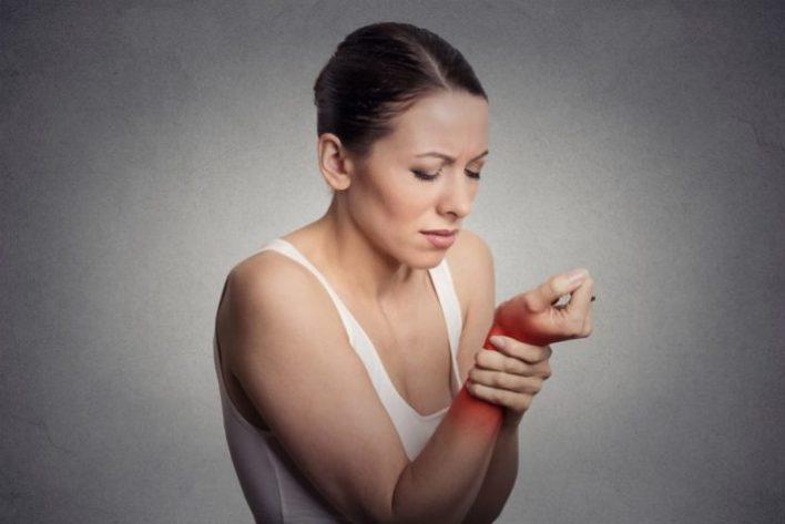 امرأة تمسك معصمها من الألم