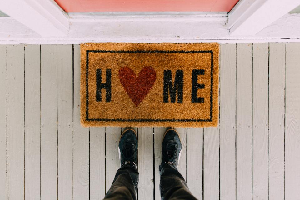 "welcome mat on porch that reads ""home"" with a heart in place of the ""o"""