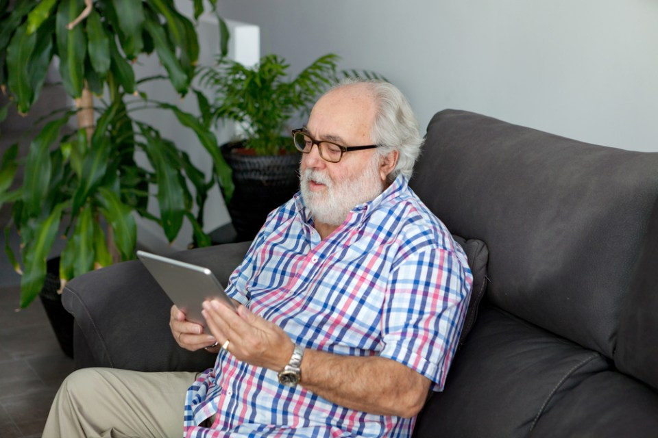 Elderly man with tablet; virtual companion care