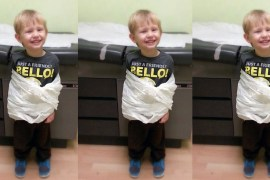 boy in Dr office wrapped in table paper