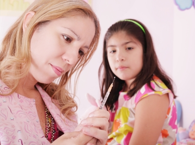 health care provider with syringe and young Latina patient