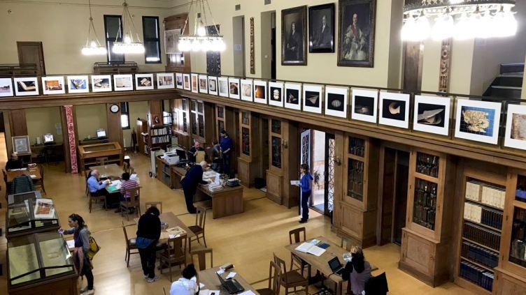 interno della Gennadius Library, alle ringhiere appese fotografie di Igo Diarra per la serie Learning from Timbuktu
