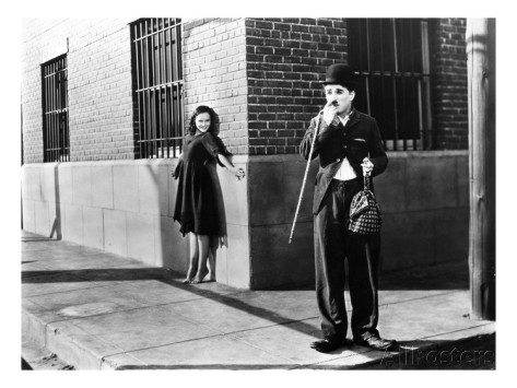 The Gamine (Paulette Goddard) sneaking up on Charlie the Tramp (Charlie Chaplin) in Modern Times
