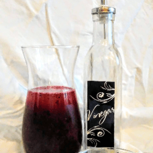 Blueberry Vinaigrette carafe with fresh blueberries and a bottle of balsamic vinaigrette