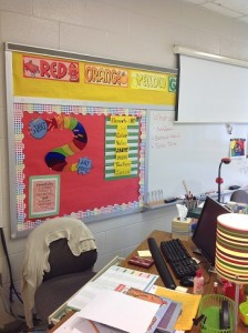 My desk with my Art Party Game on the bulletin board behind. Students earn up to three points each class to move towards having a free choice art day!