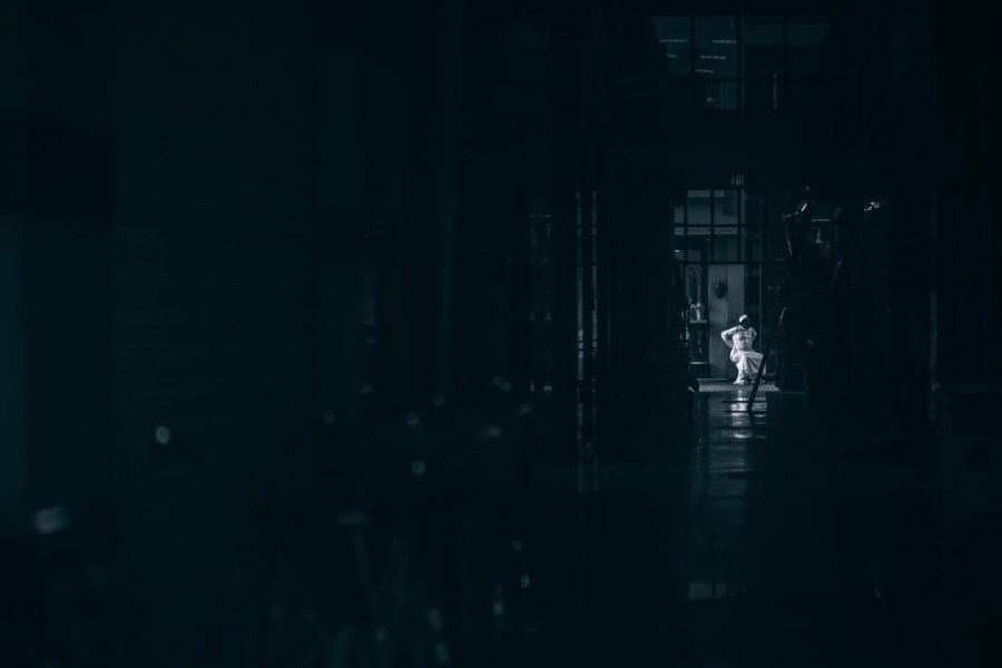 Arabic-Man-Dressed-in-White-Sitting-at-the-end-of-a-Long-Dark-Hallway
