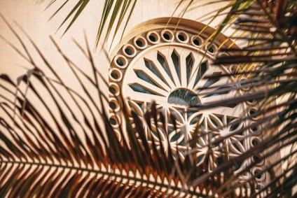 Beautifully-Designed-Islamic-Window-Photographed-Behind-Palm-Tree-Leaves
